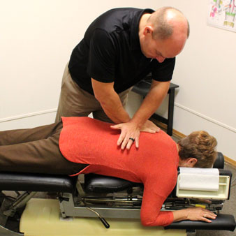 Dr. Molitor of Montgomery Family Chiropractic performing a chiropractic spinal adjustment on a patient
