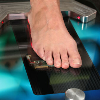 Person's bare foot resting on top of a digital foot mapping machine for custom orthodics
