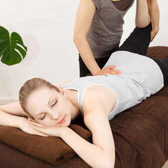 Young woman laying on a massage table while undergoing a massage therapy treatment