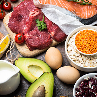 Grouping of different healthy foods - red meat, eggs, oats, fruit, fish